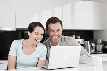 A young couple in the kitchen looking at a laptop