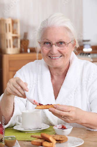 An old woman eating breakfast.