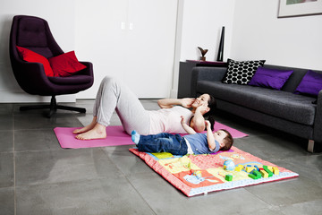 A mother and her baby son exercising at home