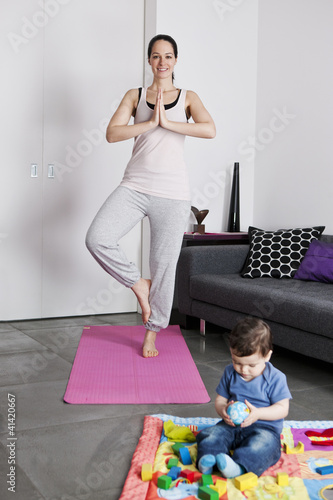 A young mother practicing yoga at home with her baby