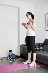 A young mother exercising at home with her baby son