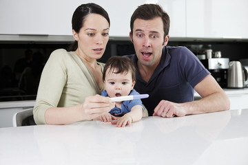 A couple and baby looking surprised at a pregnancy test result