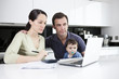 A couple and baby son looking at their household finances online