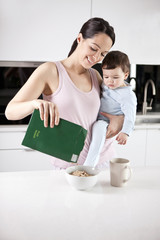 A young mother holding her baby son whilst making breakfast