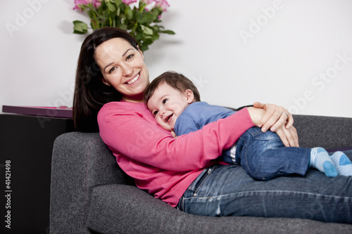 A mother cuddling her baby son on a sofa