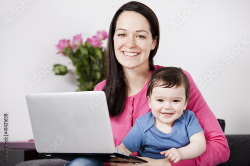 A mother using a laptop whilst holding her baby son on her lap