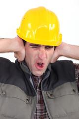 Tradesman covering his ears