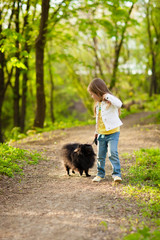 Cute little girl playing with dog in summer day