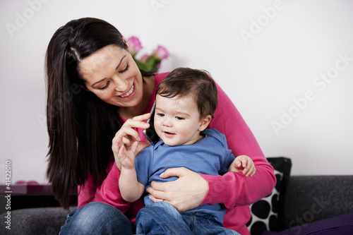 A mother and her baby son listening on a mobile phone