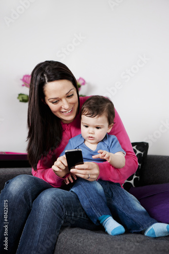 A mother and her baby son looking at a mobile phone