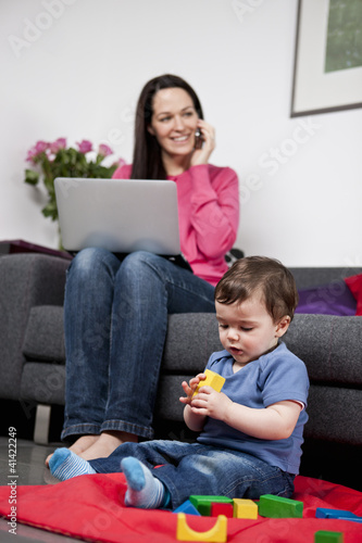 A woman using a laptop and phone at home, baby playing