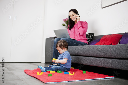 A mother using a laptop and phone, baby playing
