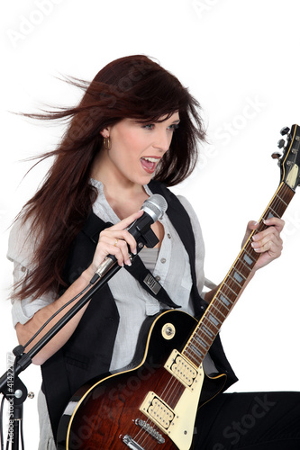 Woman singing with a guitar