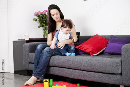 A mother sitting on a sofa winding her baby