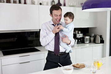 A father and his baby son looking at a telephone
