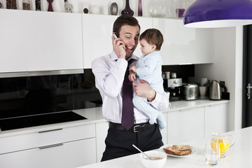 A father holding his baby son whilst speaking on the telephone