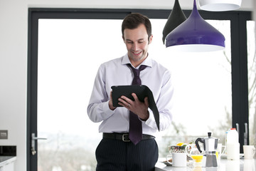 A businessman standing in a kitchen using a digital tablet