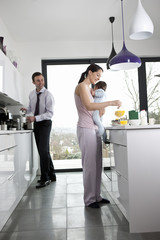 A couple and their baby son in the kitchen making breakfast