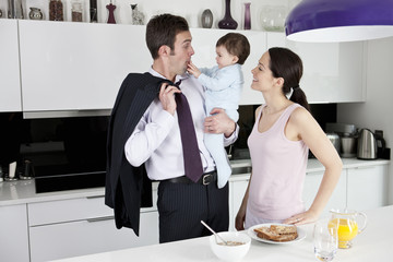 A couple and their baby son in the kitchen at breakfast time