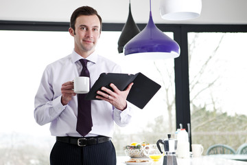 A businessman in a kitchen holding a cup and a digital tablet