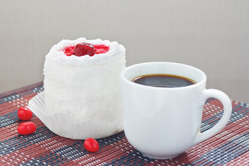 Cup of coffee and cream cake with cherries