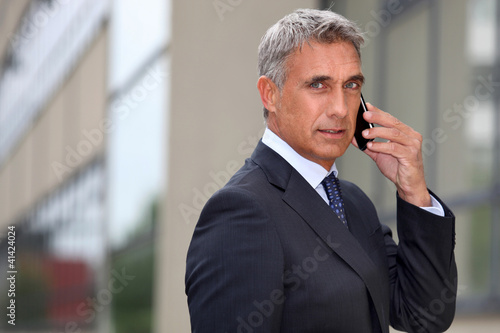 Mature businessman using a cellphone outside