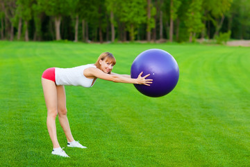 Young  woman doing fitness exercises with fit ball, outdoor