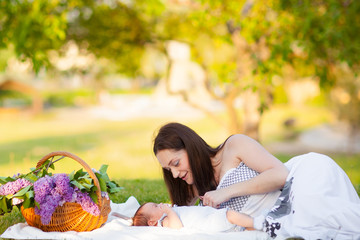 Happy  mother and baby resting in summer park