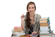 Female student sat at desk with books