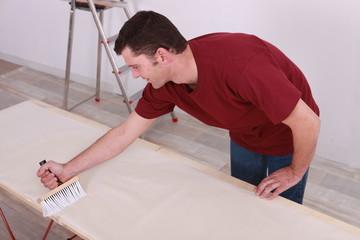 Man gluing paper
