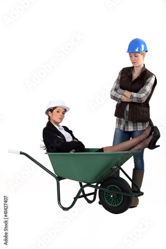 Architect laying in wheelbarrow whilst worker watches