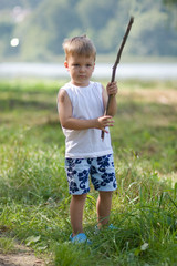 boy with a stick in hands, on the bank of the lake