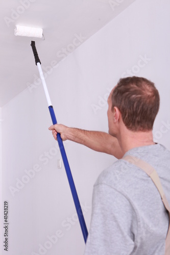 Decorator painting a ceiling white