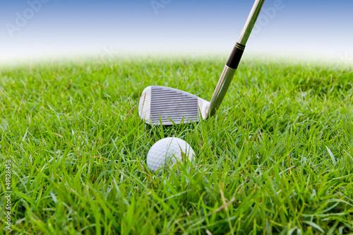 golf ball and iron on tall grass