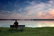 Mann auf Bank am See