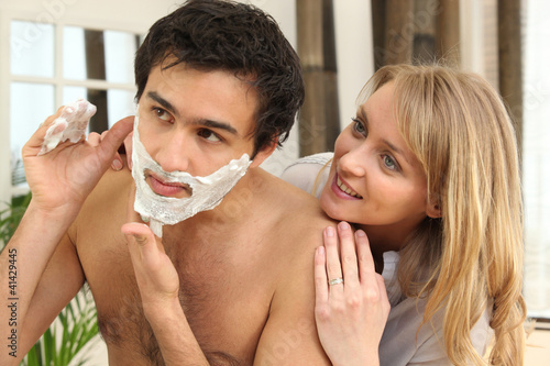 Woman looking at man shaving