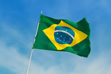 Brazil flag flutters against Brazilian blue skies