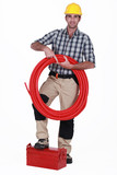 Tradesman holding tubing and propping a toolbox poster