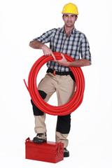 Tradesman holding tubing and propping a toolbox