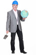 Man in suit holding globe and trowel