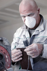 Man wearing mask whilst sanding