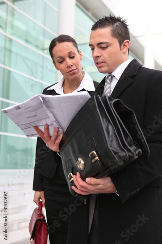 Businesspeople looking at a plan outdoors