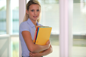 Young blonde with folders in the arms