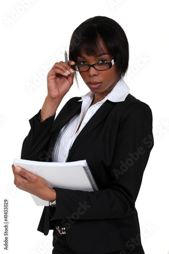 Serious businesswoman looking over her glasses