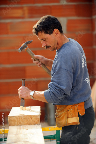 Man using chisel and haller on wooden block