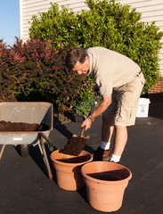 Senior man digging soil in wheelbarrow