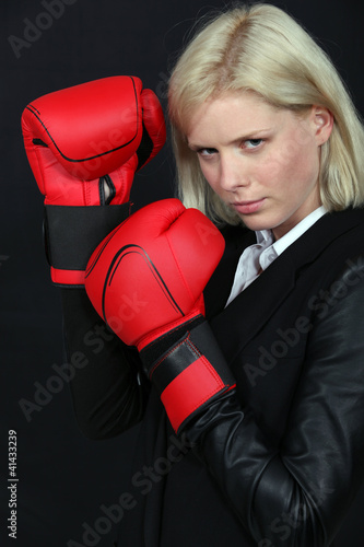 Businesswoman holding boxing gloves