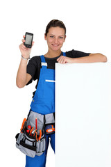 Woman with blank board, toolbelt and cellphone