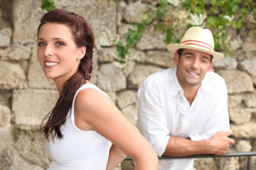 Couple standing by a stone wall