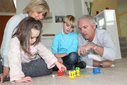 Elderly couple playing with their grandchildren